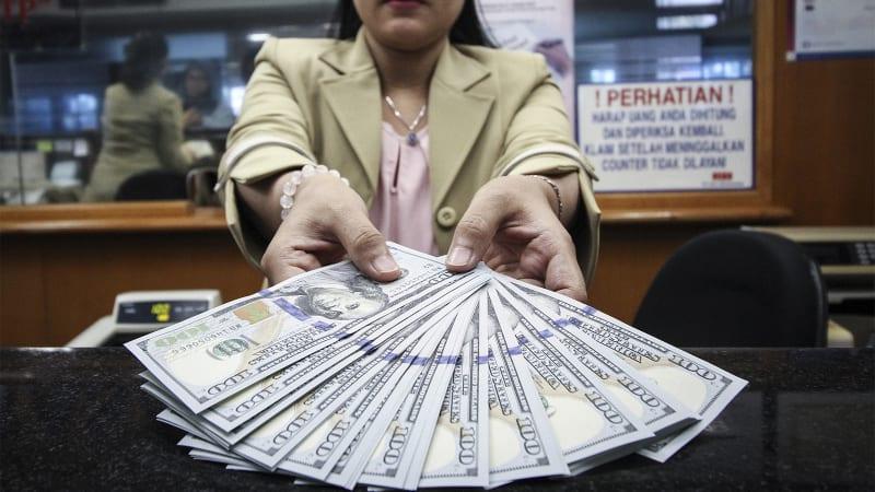 Petugas menunjukan uang dolar AS.
