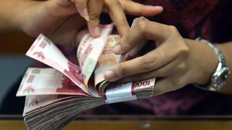Ilustrasi menghitung uang Rupiah.