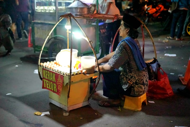 Penjual kerak telor berjualan di pintu keluar DWP