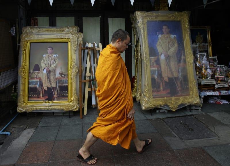 Seorang Biksu Berjalan di Antara Foto Raja Thailand Maha Vajiralongkorn